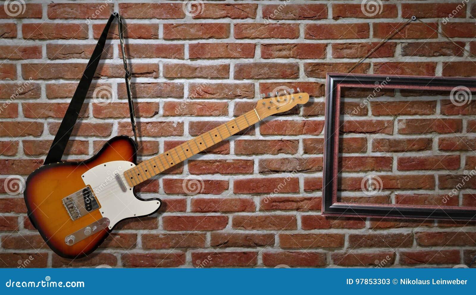 Una guitarra eléctrica está colgando en una pared de ladrillo