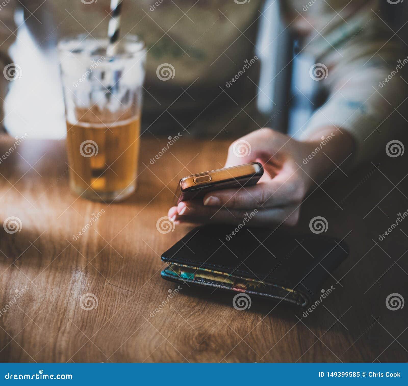 Una hembra blanca sent? la cerveza de jengibre abajo de consumici?n mientras que en su tel?fono m?vil en un ambiente brillante
