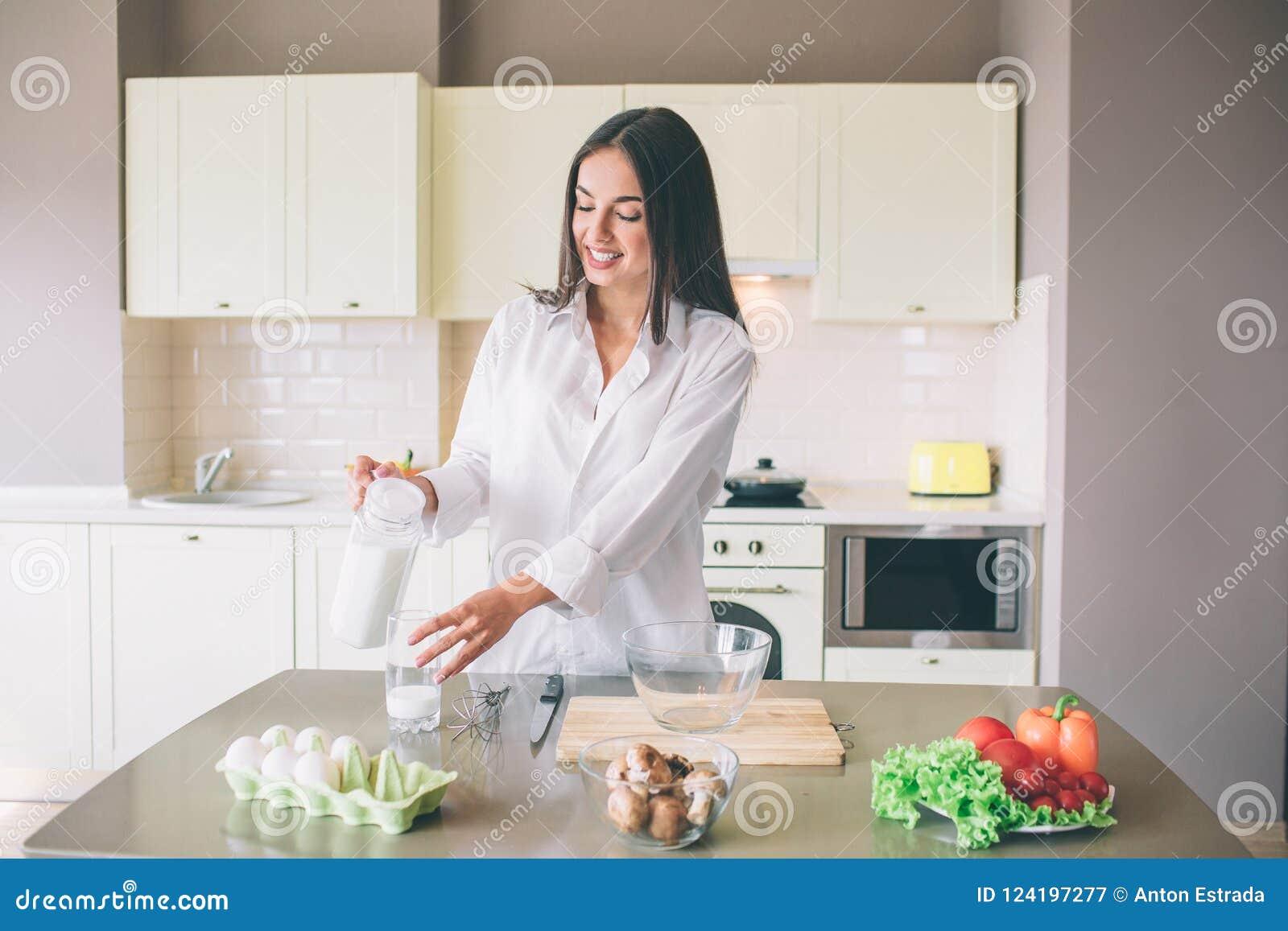 Una imagen de la muchacha hermosa que se coloca en cocina y leche de colada en la taza de cristal Ella está mirando lo y la sonri
