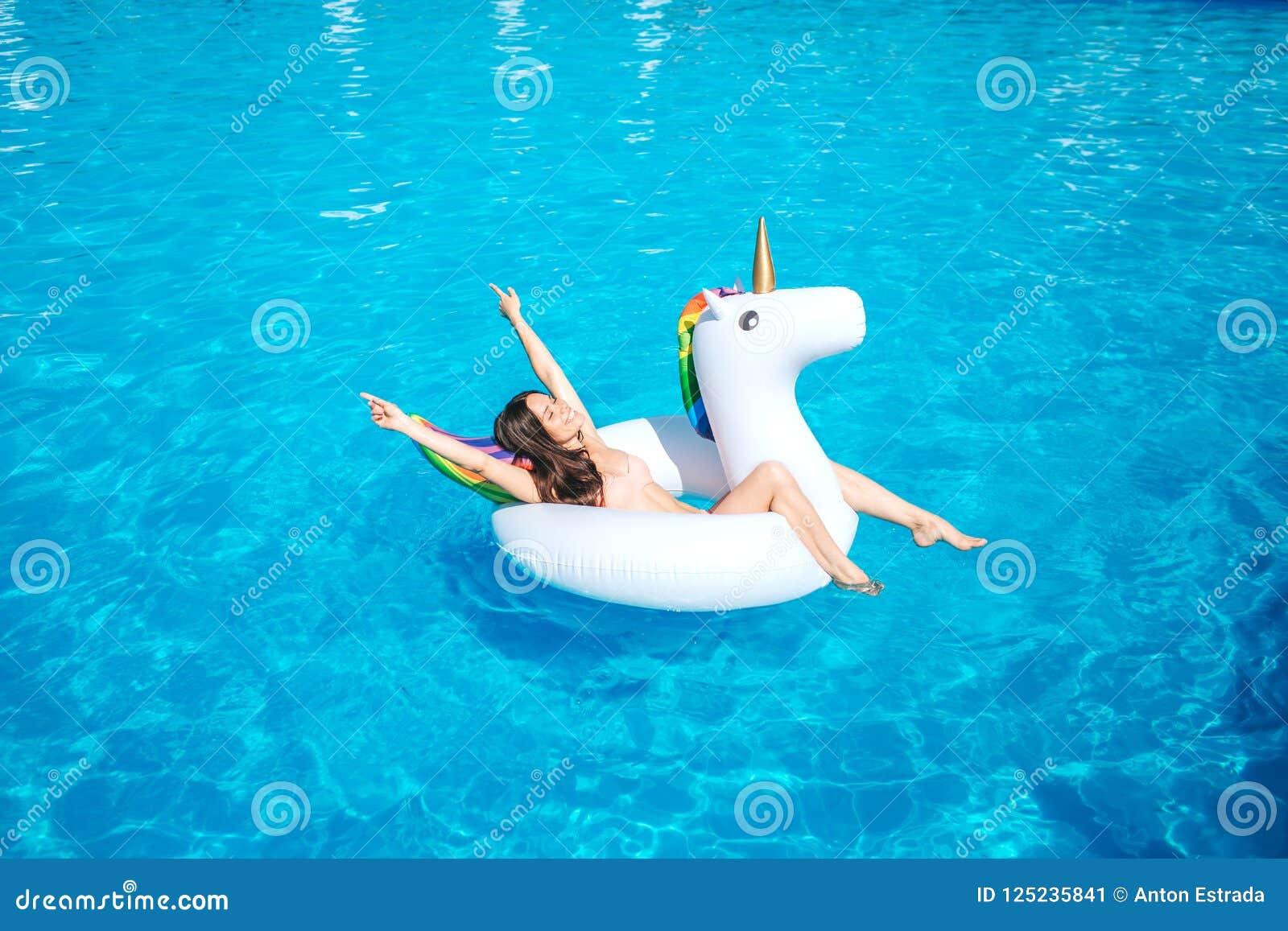 Una imagen de la natación de la muchacha en piscina solamente Ella miente en el colchón de aire y presenta Reclinación del OS de