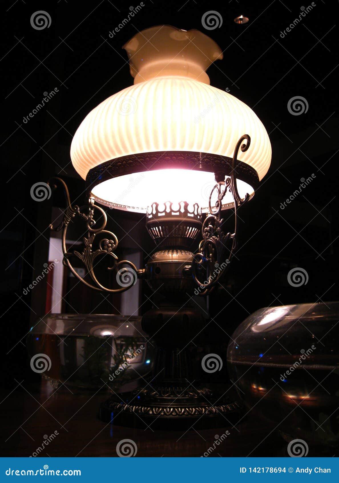 Una lámpara de cobre amarillo pasada de moda elegante que brilla suavemente de la esquina oscura cerca de mi tabla en el restaura