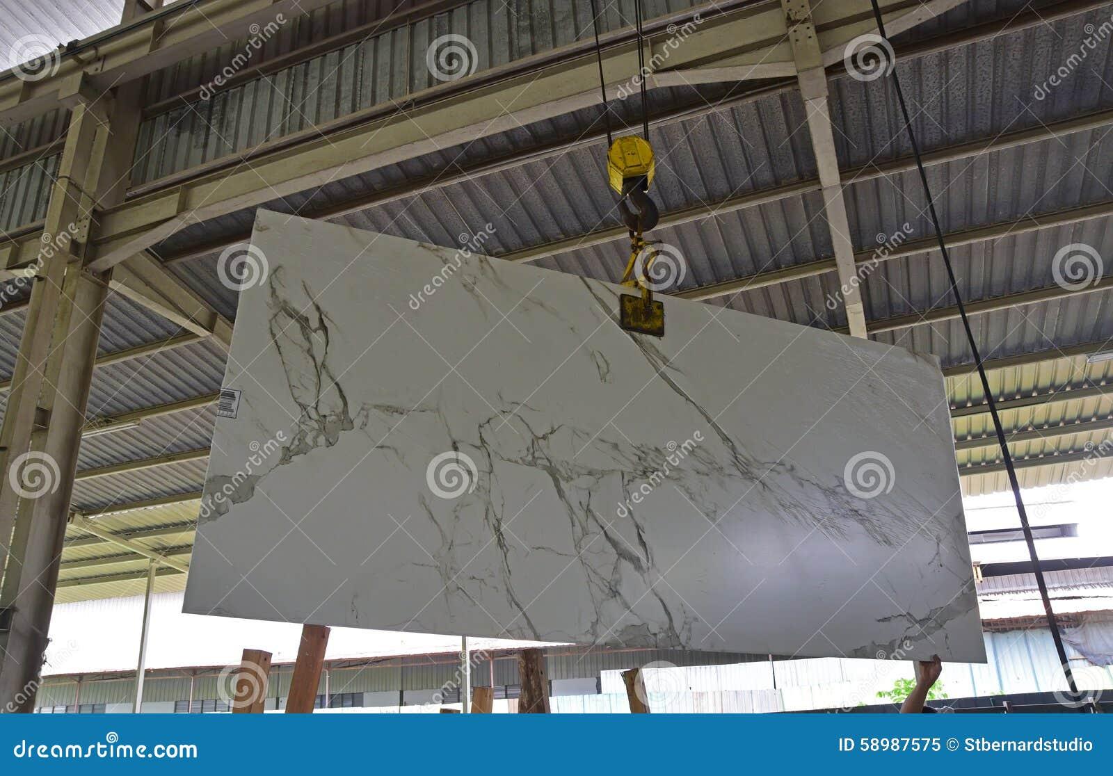 Una lastra di pietra recentemente arrivata sta essendo ascensore da indicare al cliente