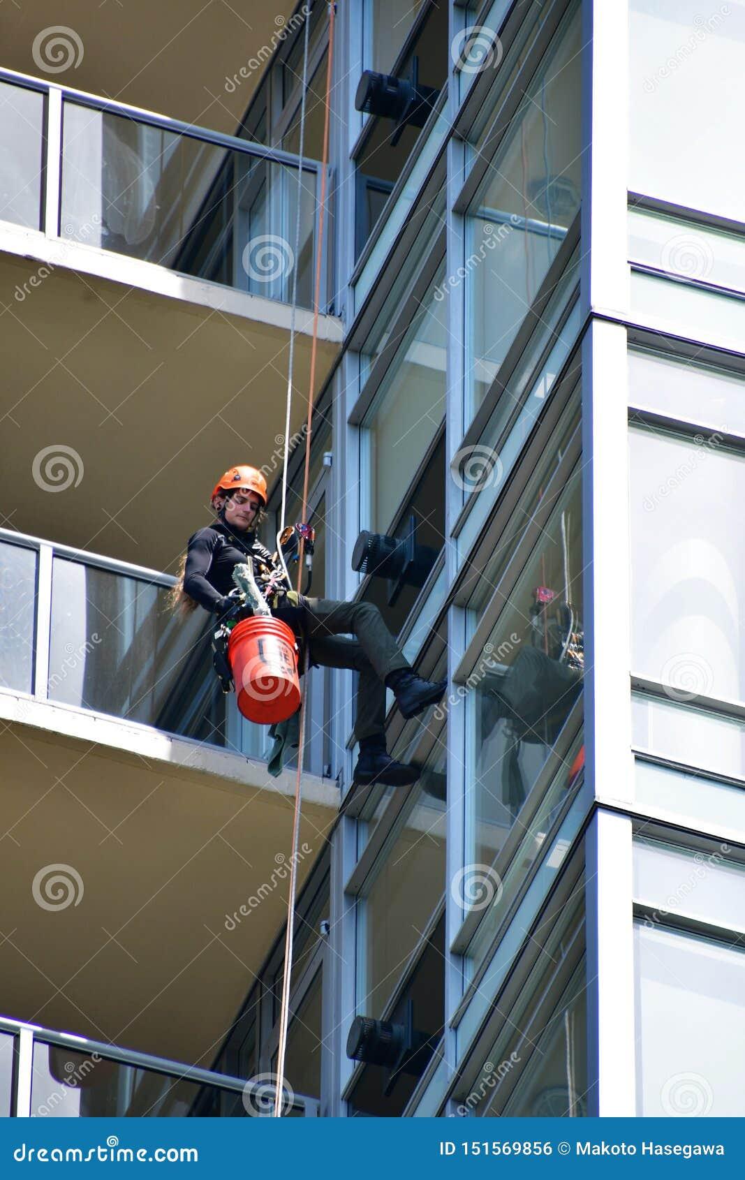 Una lavadora de ventana que limpia la ventana de un alto edificio de la subida