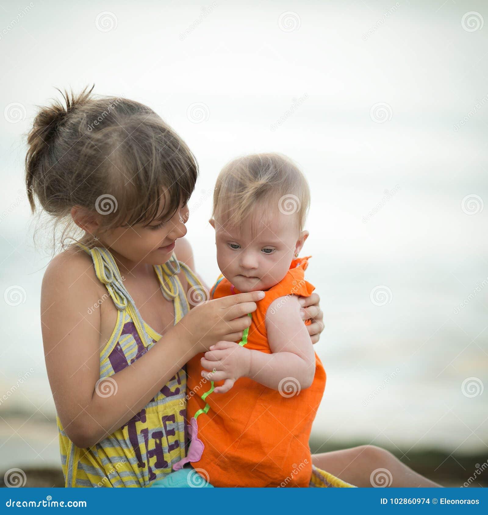 Una más vieja hermana detiene a una muchacha hermosa con Síndrome de Down