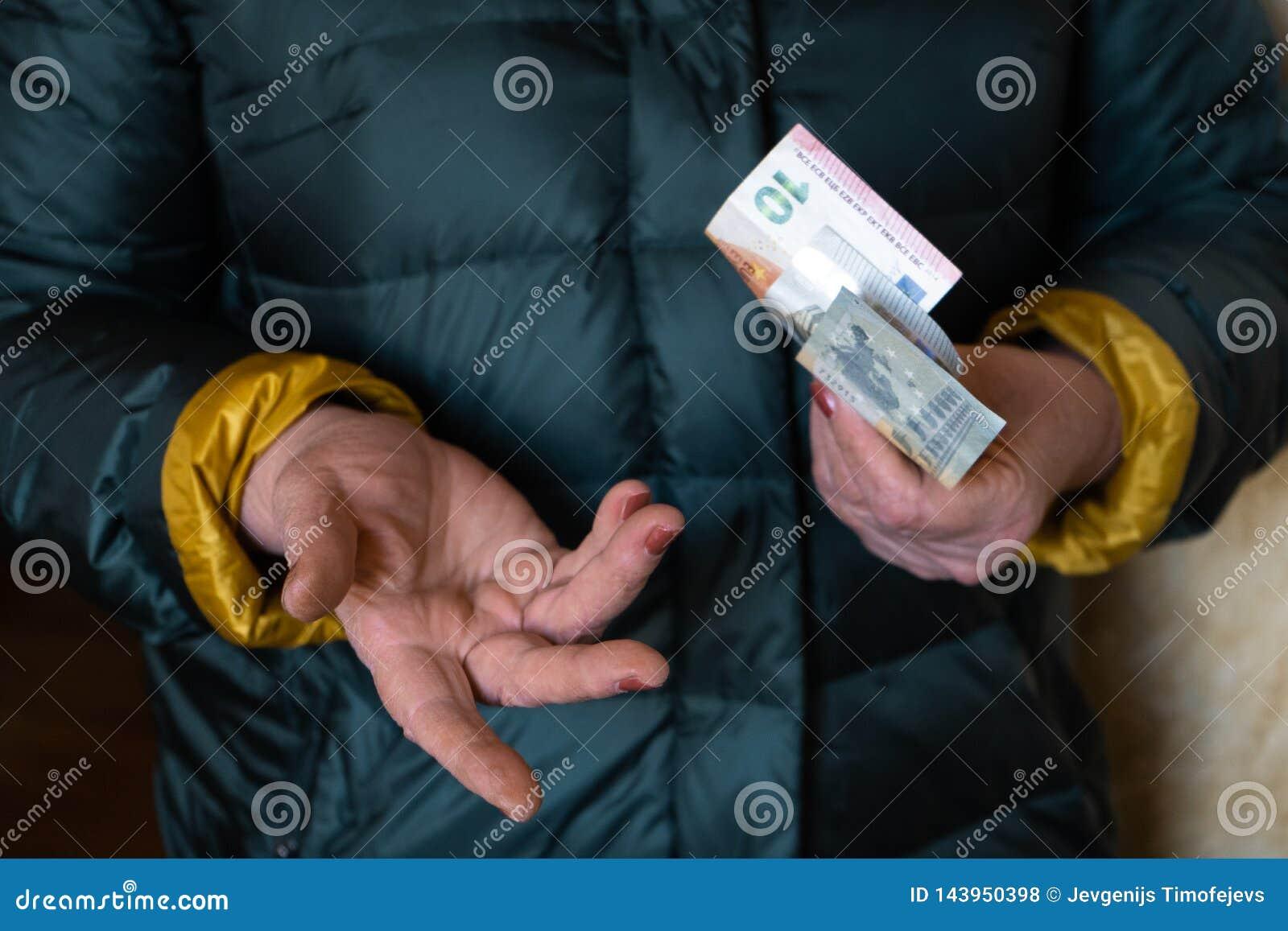 Una más vieja mujer mayor sostiene los billetes de banco EURO - del este - pensión europea del sueldo