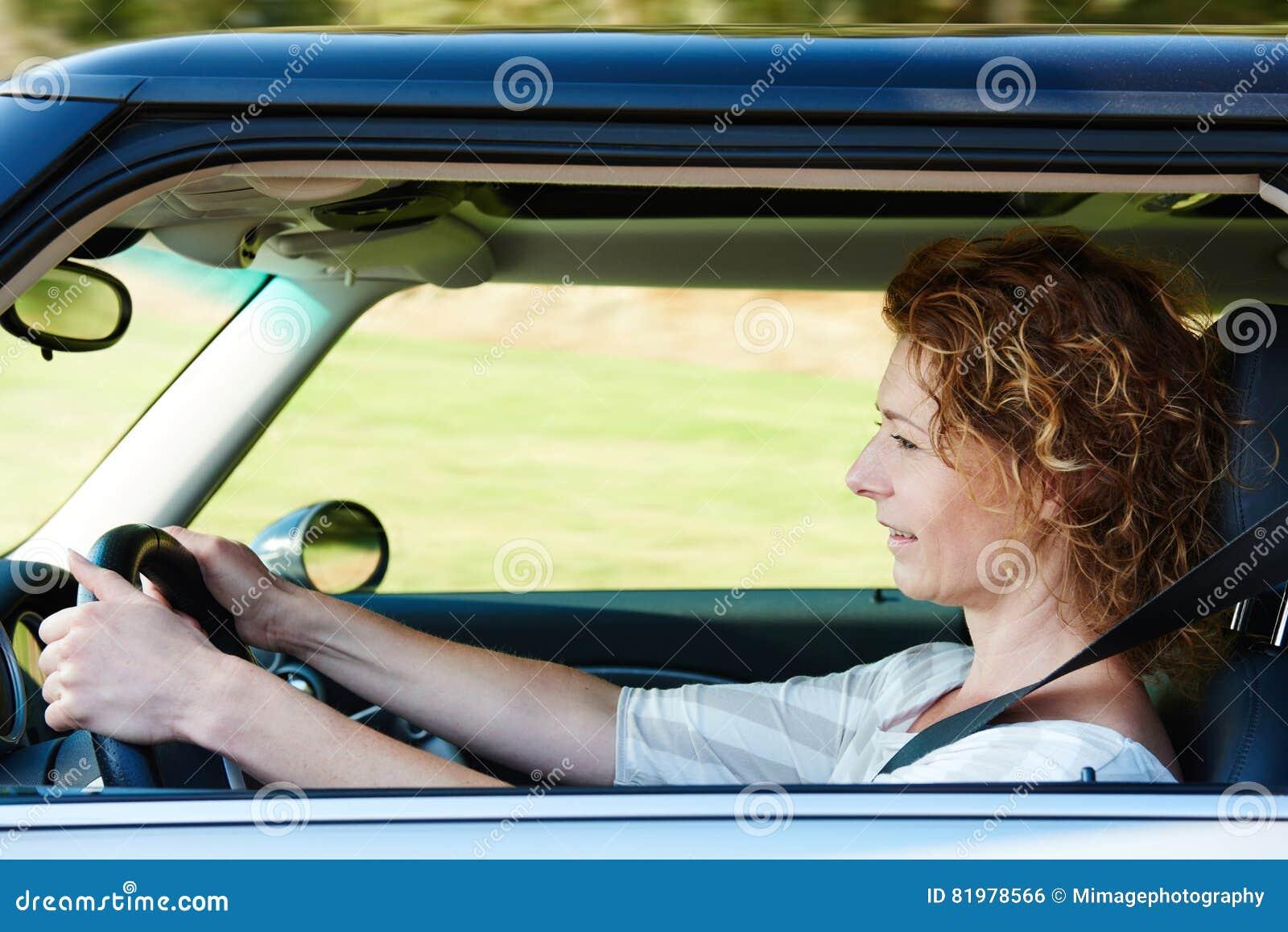 Una más vieja mujer que conduce el coche