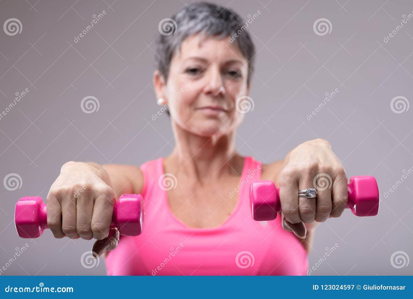Una más vieja mujer que se resuelve con un par de pesas de gimnasia