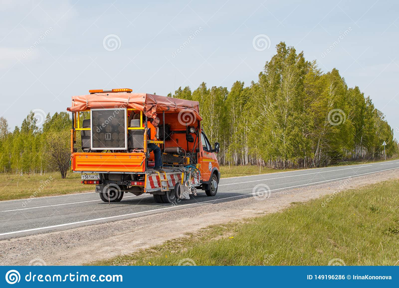 Una macchina di segno applica le marcature orizzontali su una strada con pittura