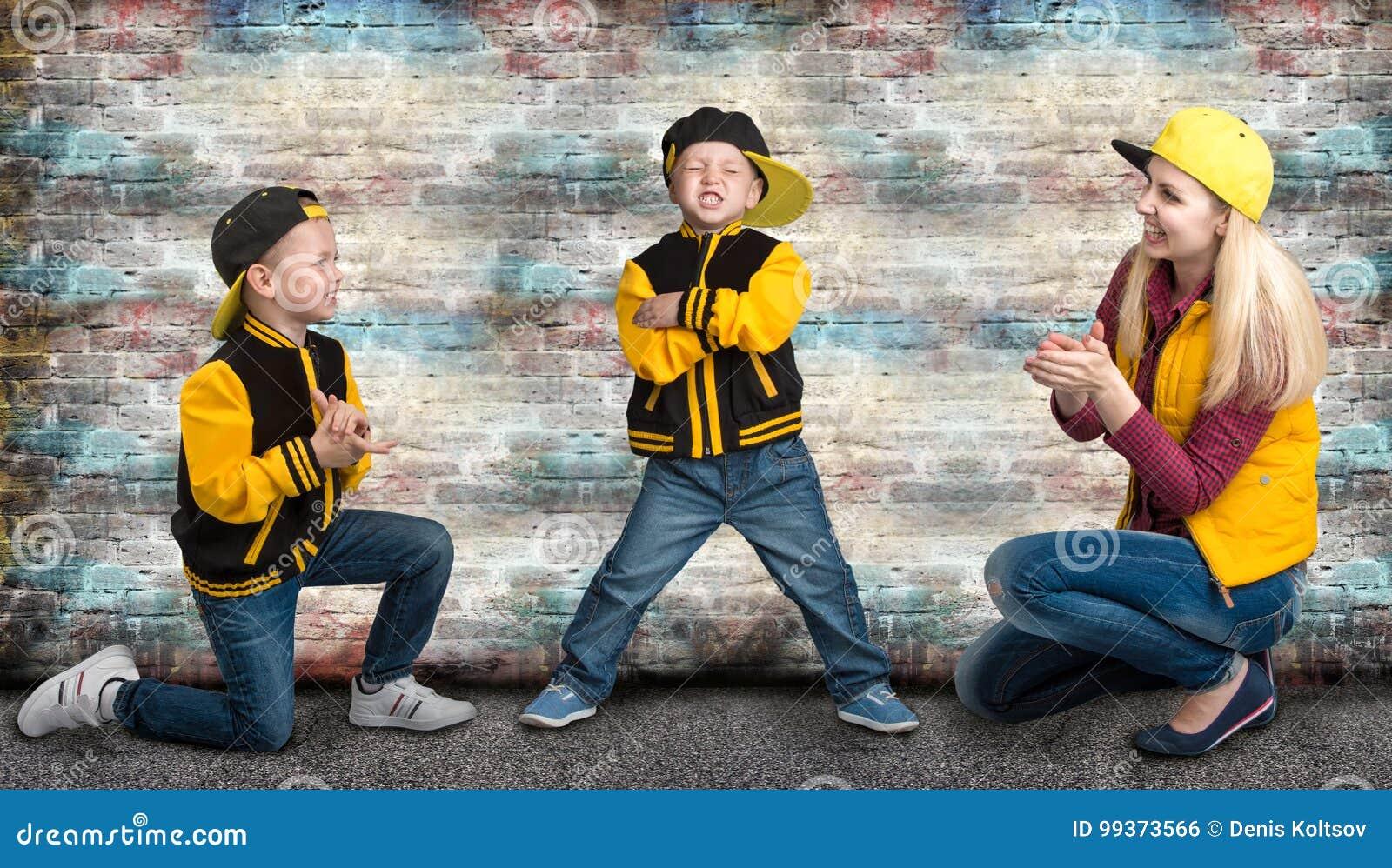 Una madre giovane e due giovani figli nello stile di hip-hop Famiglia alla moda Graffiti sulle pareti