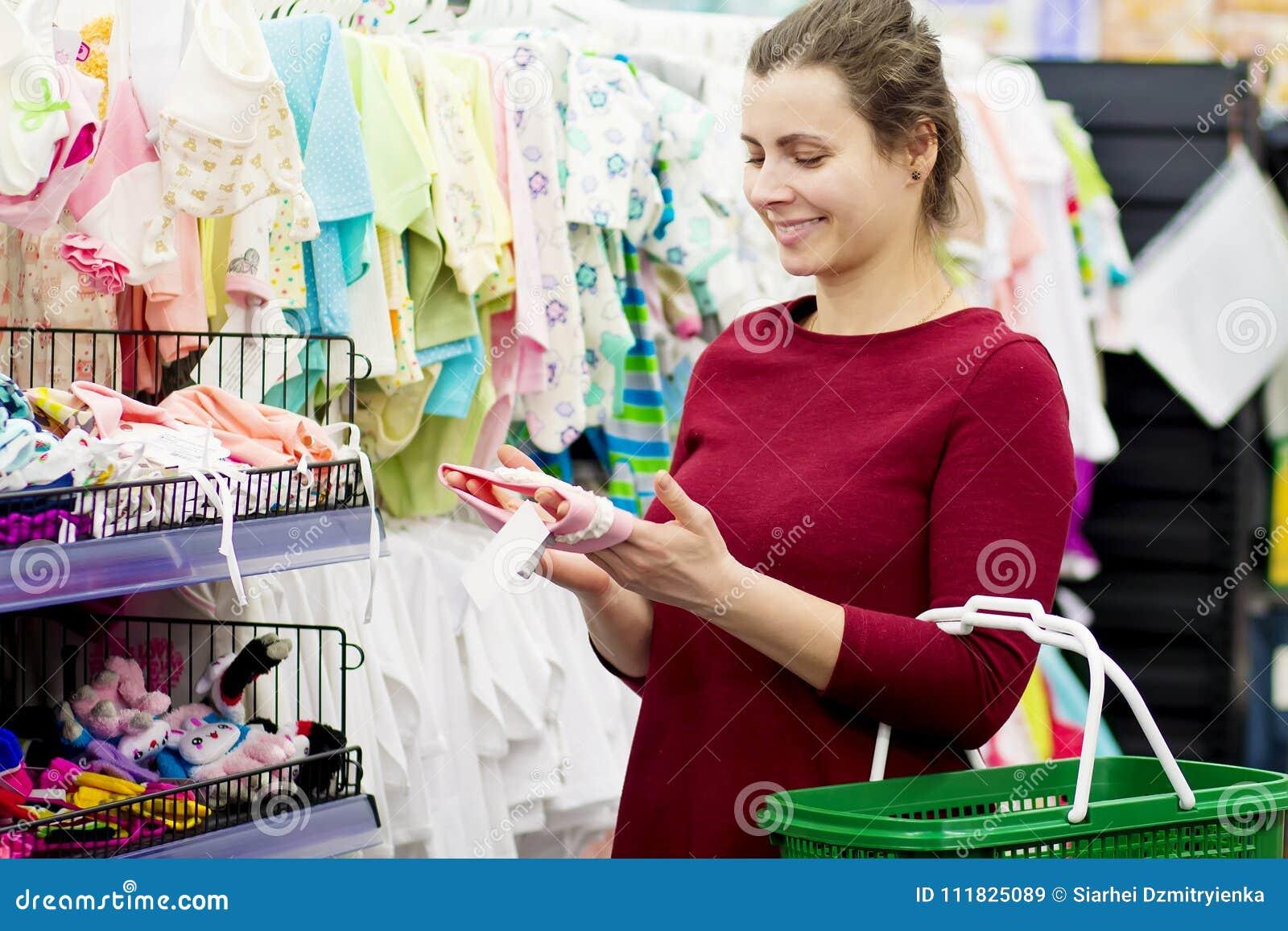 5e7f5b3ea Una madre joven compra ropa para su bebé en una tienda de ropa del ` s de  los niños La muchacha elige la ropa en la alameda Concepto de la ropa de ...