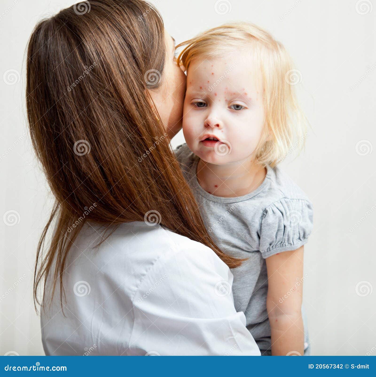 Una madre sta tenendo una ragazza ammalata.
