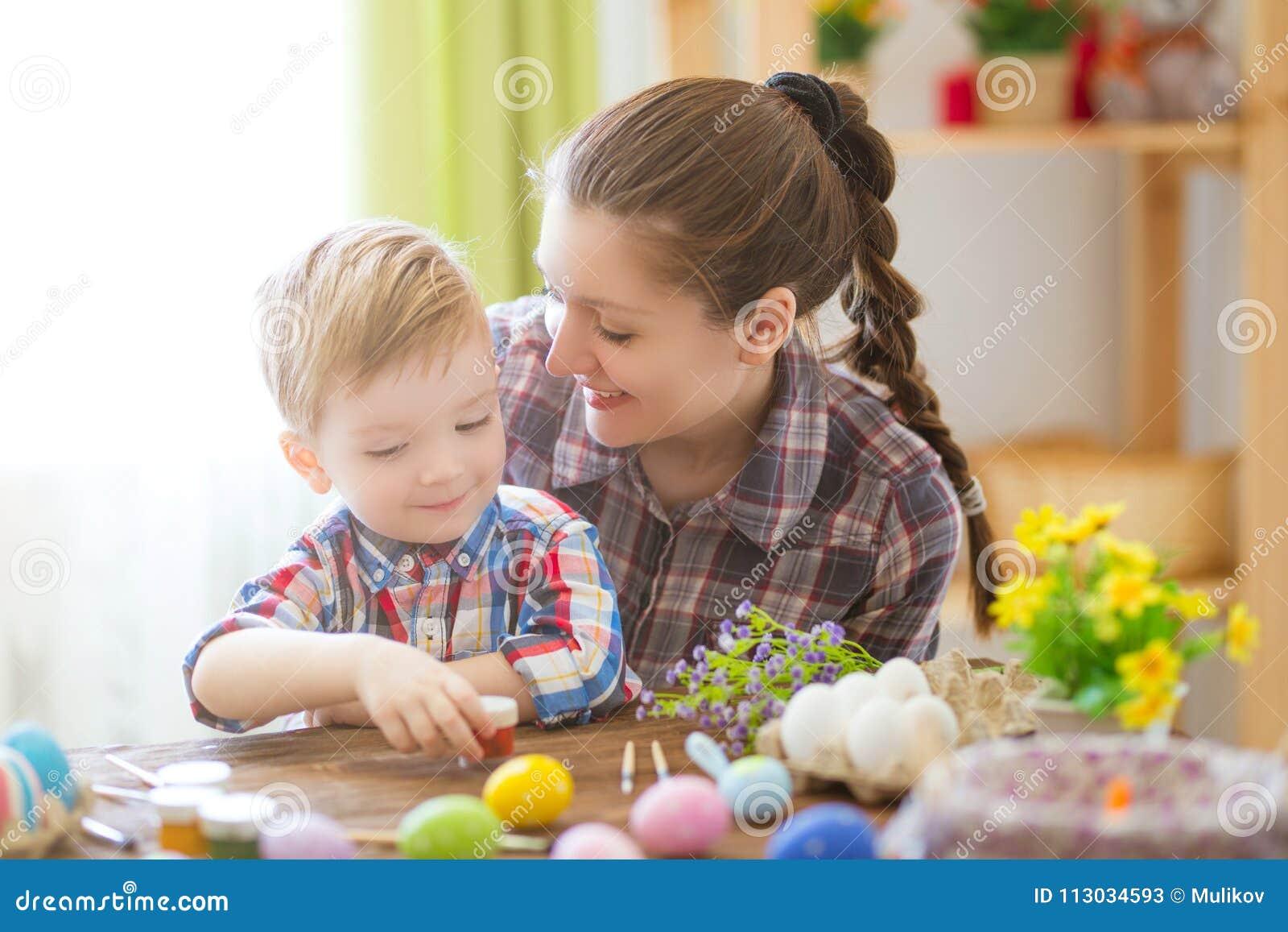Una madre y su hijo que pintan los huevos de Pascua Familia feliz que se prepara para Pascua Pascua feliz