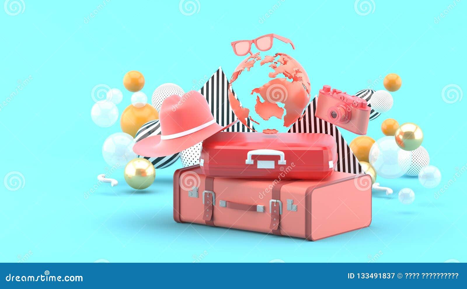 Una maleta debajo del globo rodeado por una cámara y un sombrero en un fondo azul