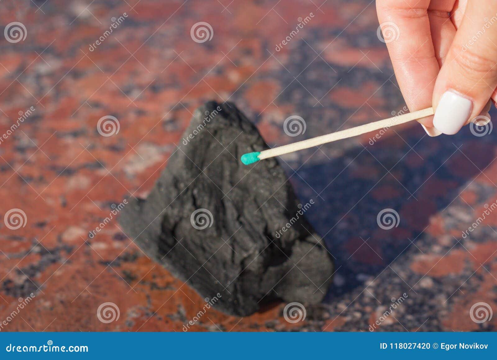 Una mano de la hembra lleva a cabo un partido, en un fondo borroso del carbón duro