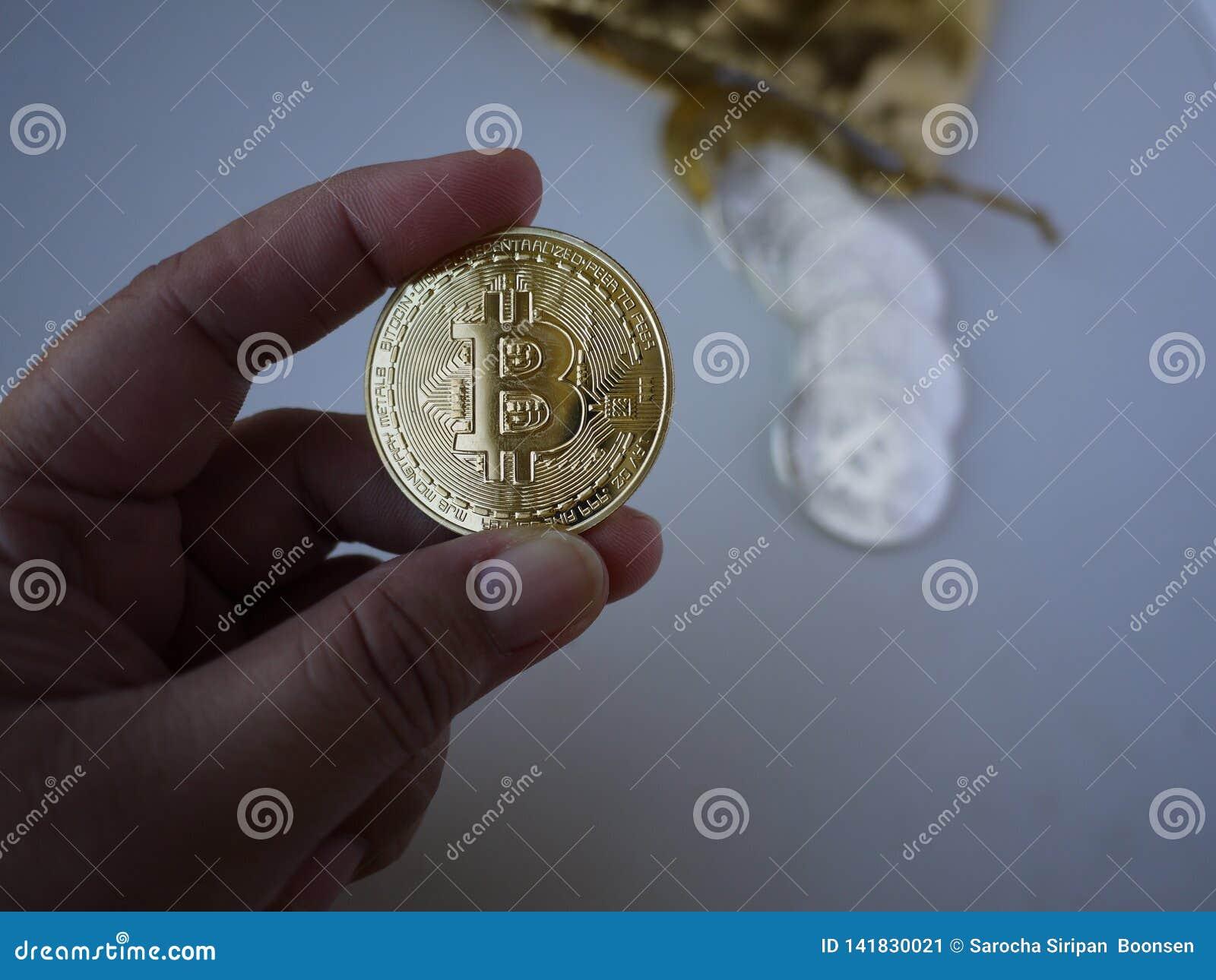 Una mano de la señora está asiendo un bitcoin de oro
