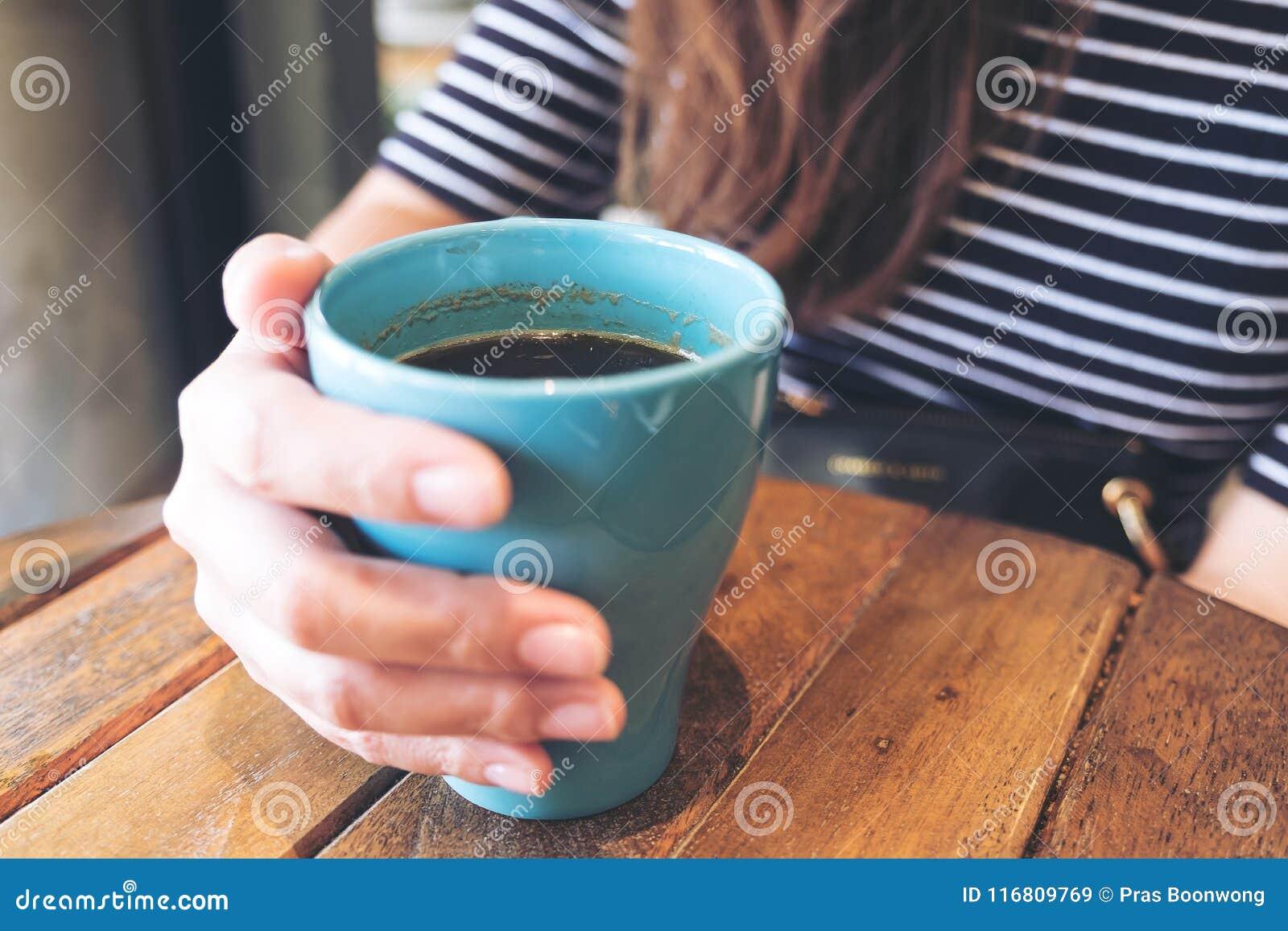 Una mano del ` s della donna che tiene tazza blu di caffè caldo sulla tavola di legno d annata in caffè