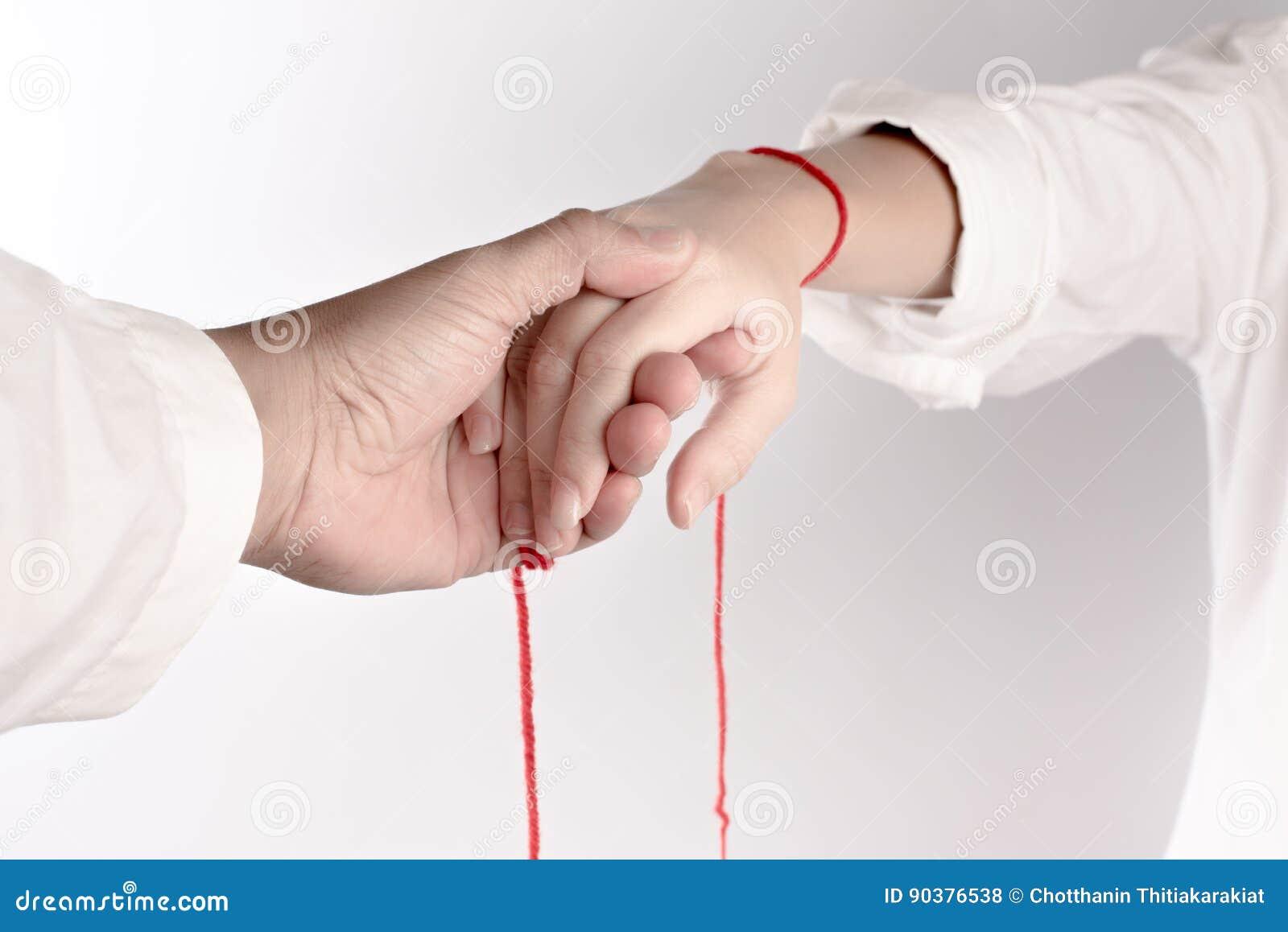 Una mano del tacto de los pares La fe del hilo rojo trae destino
