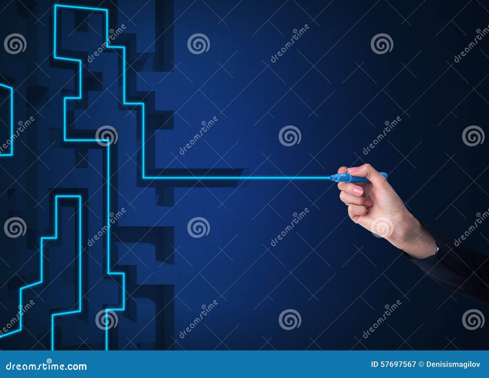 Una mano está dibujando una línea como solución del laberinto