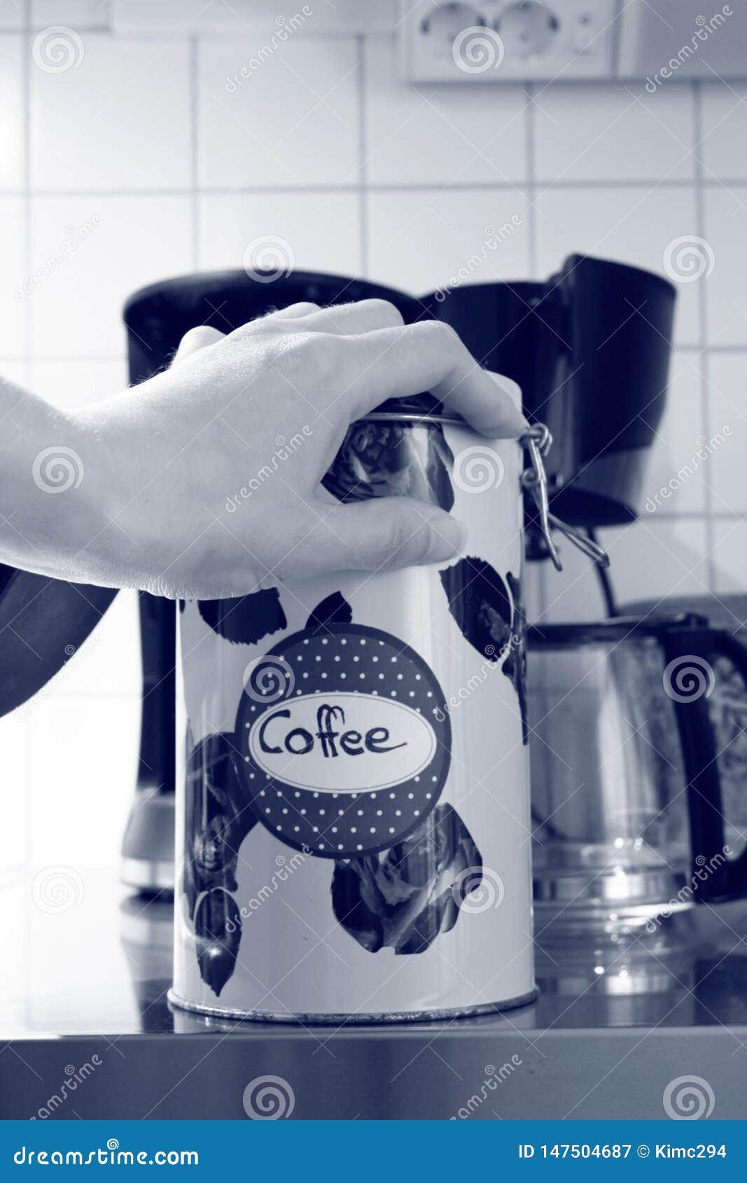 Una mano miente encima de una lata del café