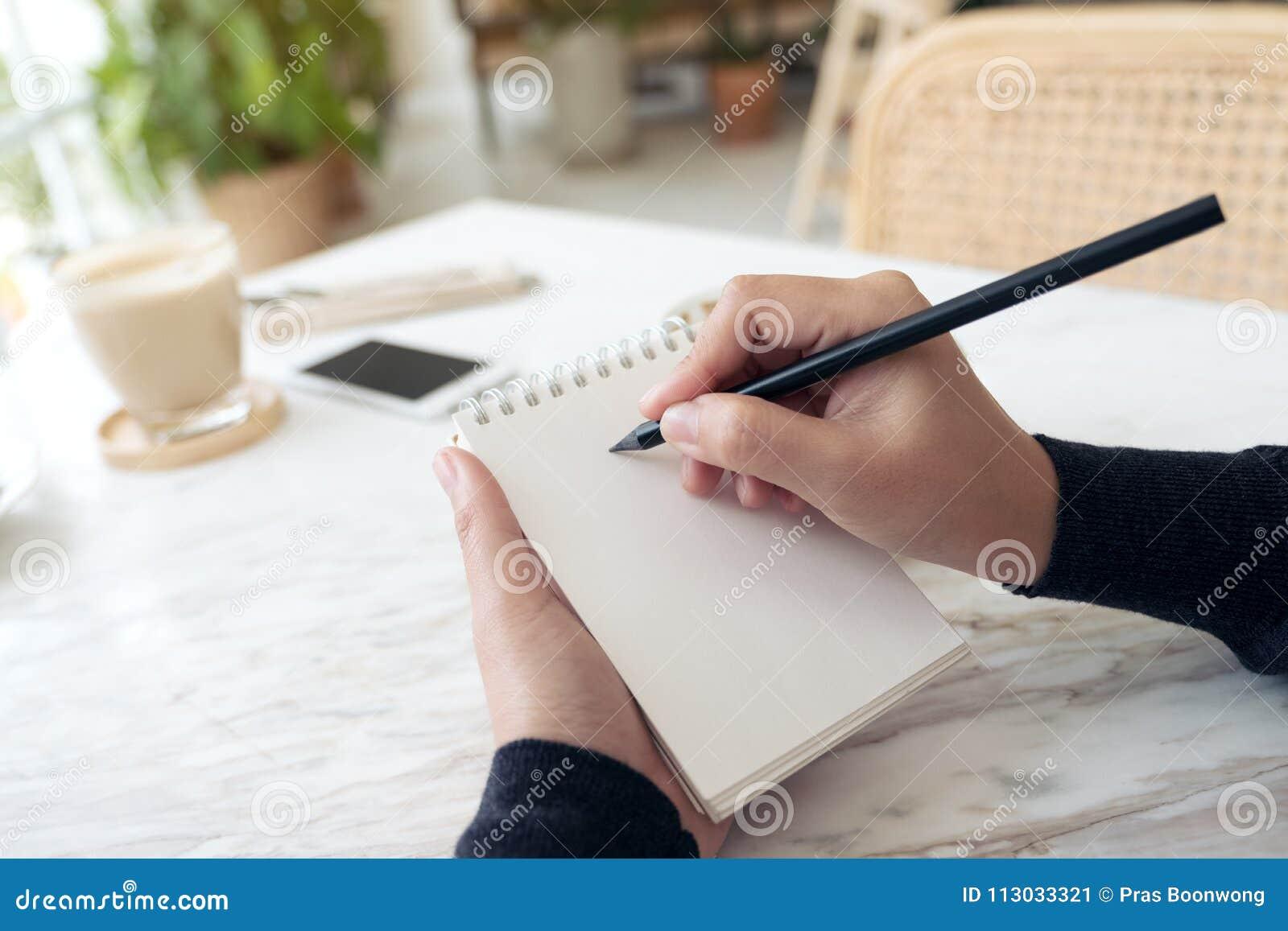Una mano que anota en un cuaderno en blanco blanco con la taza y el postre de café en la tabla en café