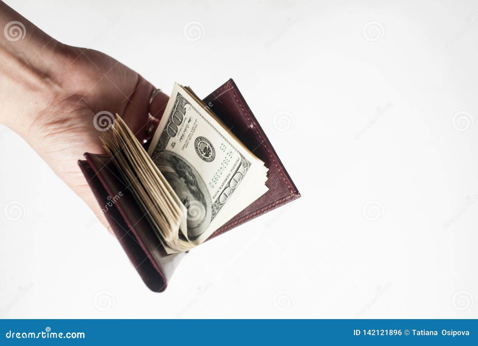 Una mano que lleva a cabo una cartera por completo de cientos billetes de dólar aislados sobre un fondo blanco