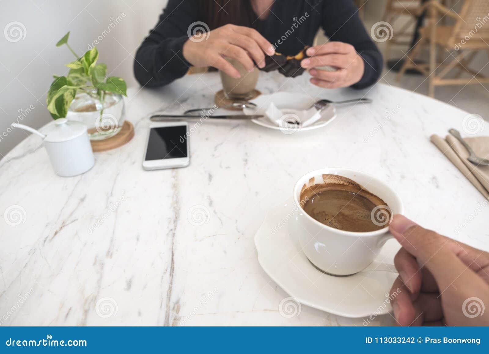 Una mano que sostiene la taza de café y una mujer que come el bocado en la tabla de cristal en café moderno