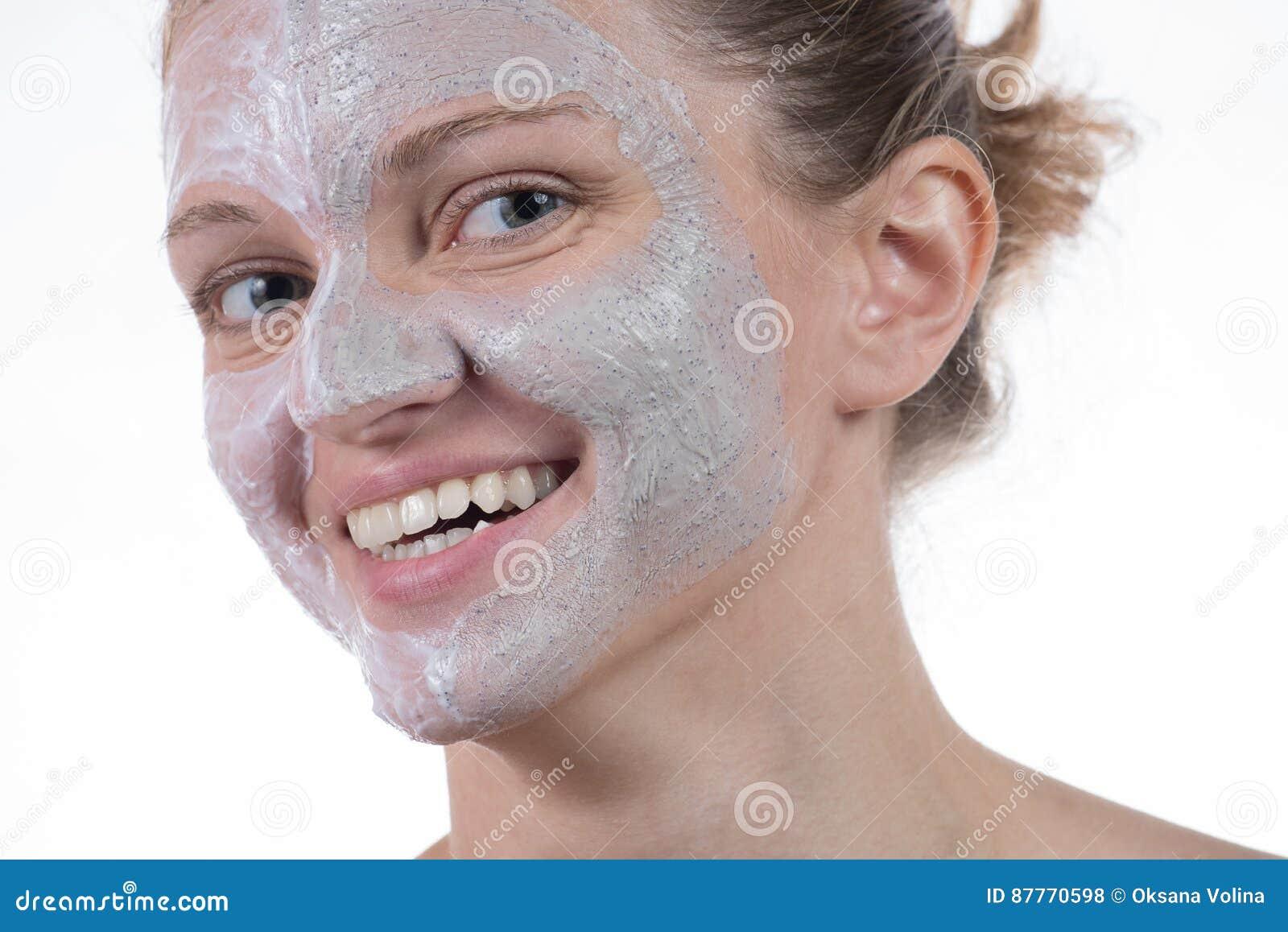 Una maschera di due cosmetici di argilla grigia con sfrega e screma sul fronte