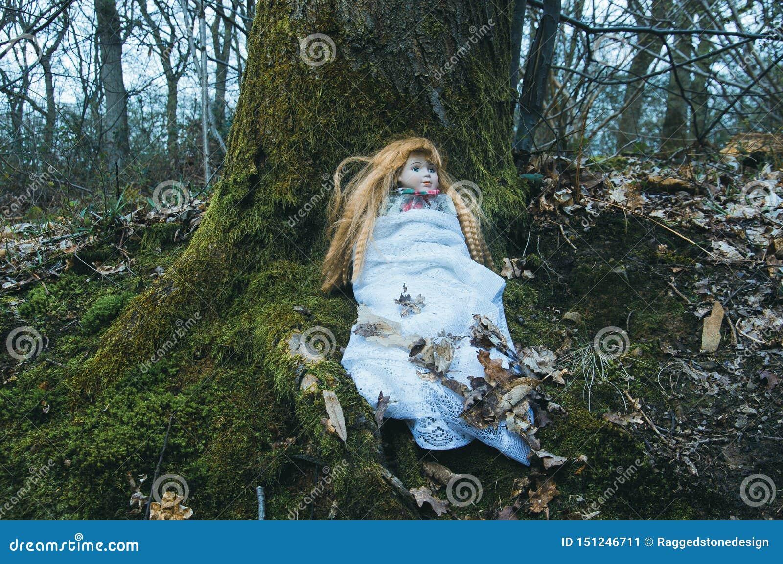 Una muñeca fantasmagórica ceepy, sentándose en un bosque en invierno Con una oscuridad, muda corrija