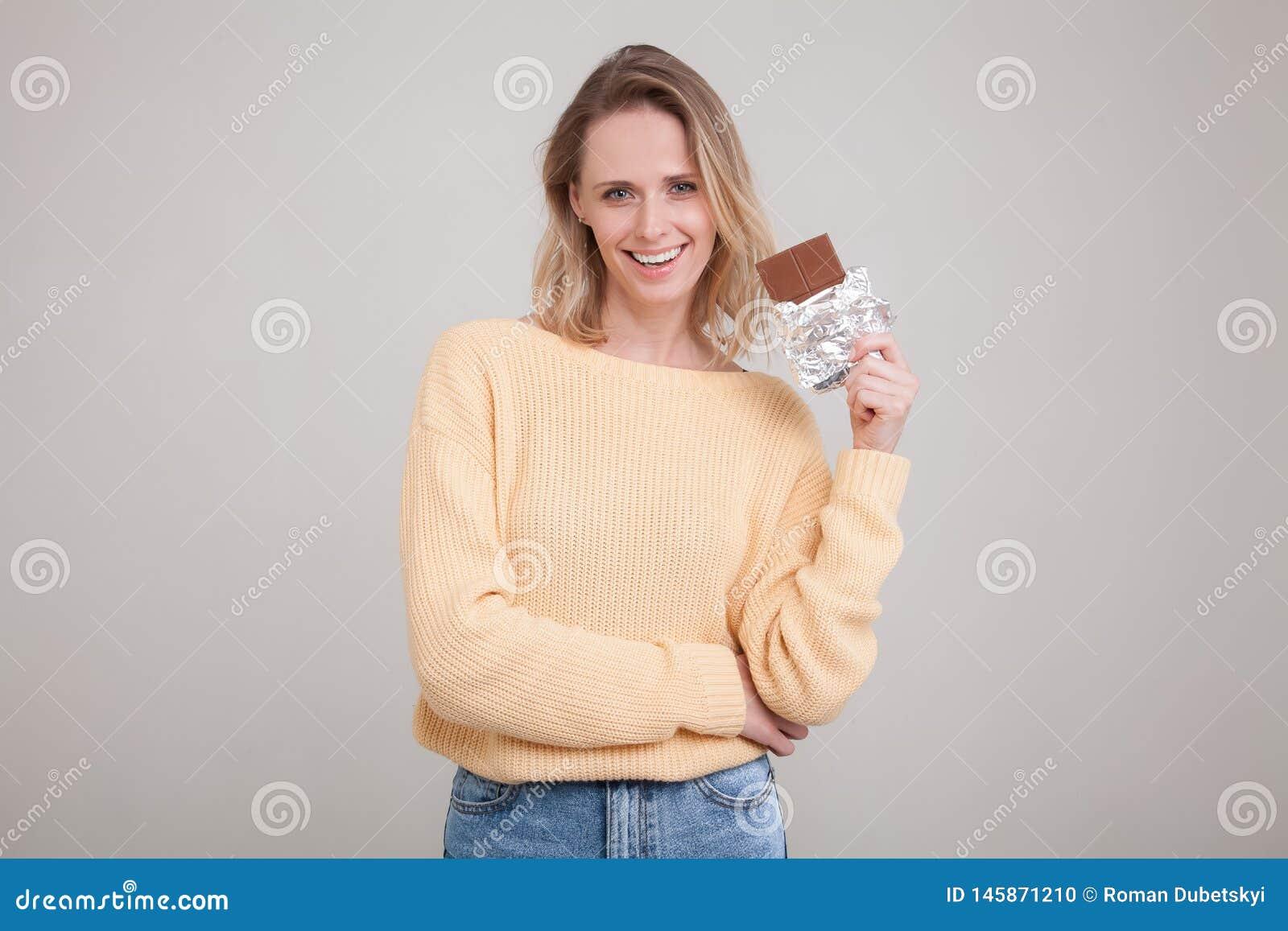Una muchacha blanda joven hermosa con el pelo rubio sostiene una barra de chocolate en la cara que ella est? llevando en un su?te