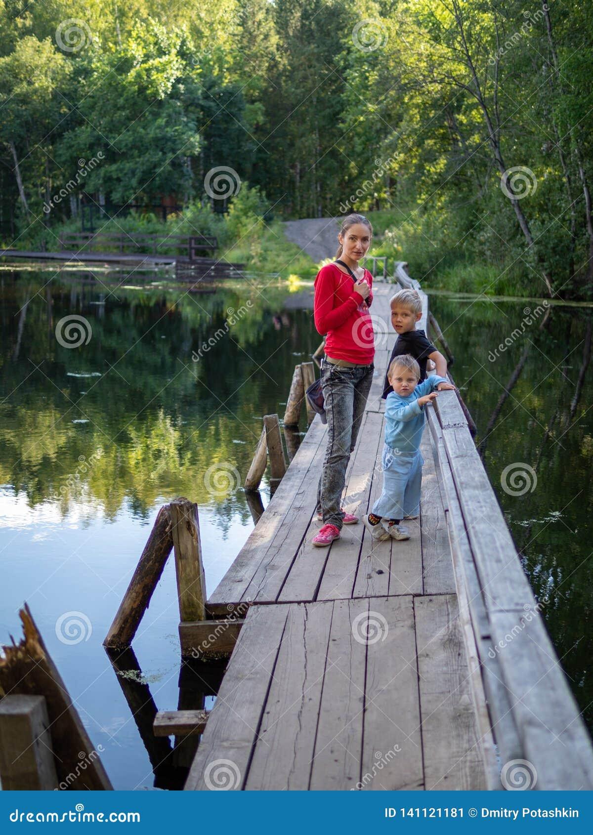 Una muchacha con dos niños se está colocando en el puente de madera viejo a través de un río reservado