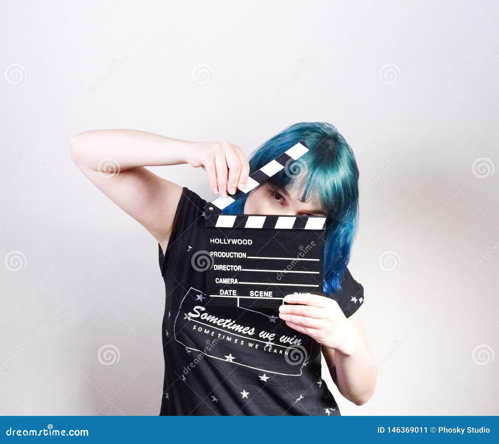 Una muchacha con el pelo azul, sosteniendo una chapaleta