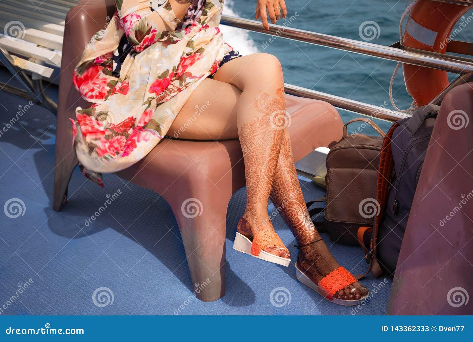 Una muchacha con los tatuajes temporales de la alheña en sus piernas Se sienta en vestido colorido en una silla en un barco de cr