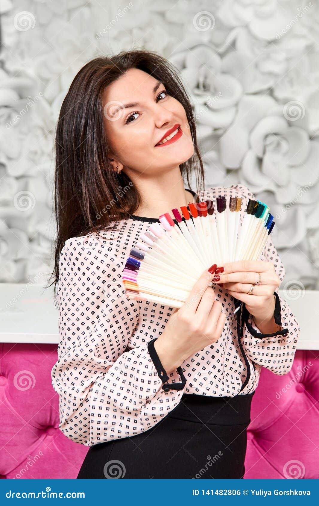 Una muchacha con una manicura hermosa, sosteniendo muestras de manicura y de sonrisa Morena