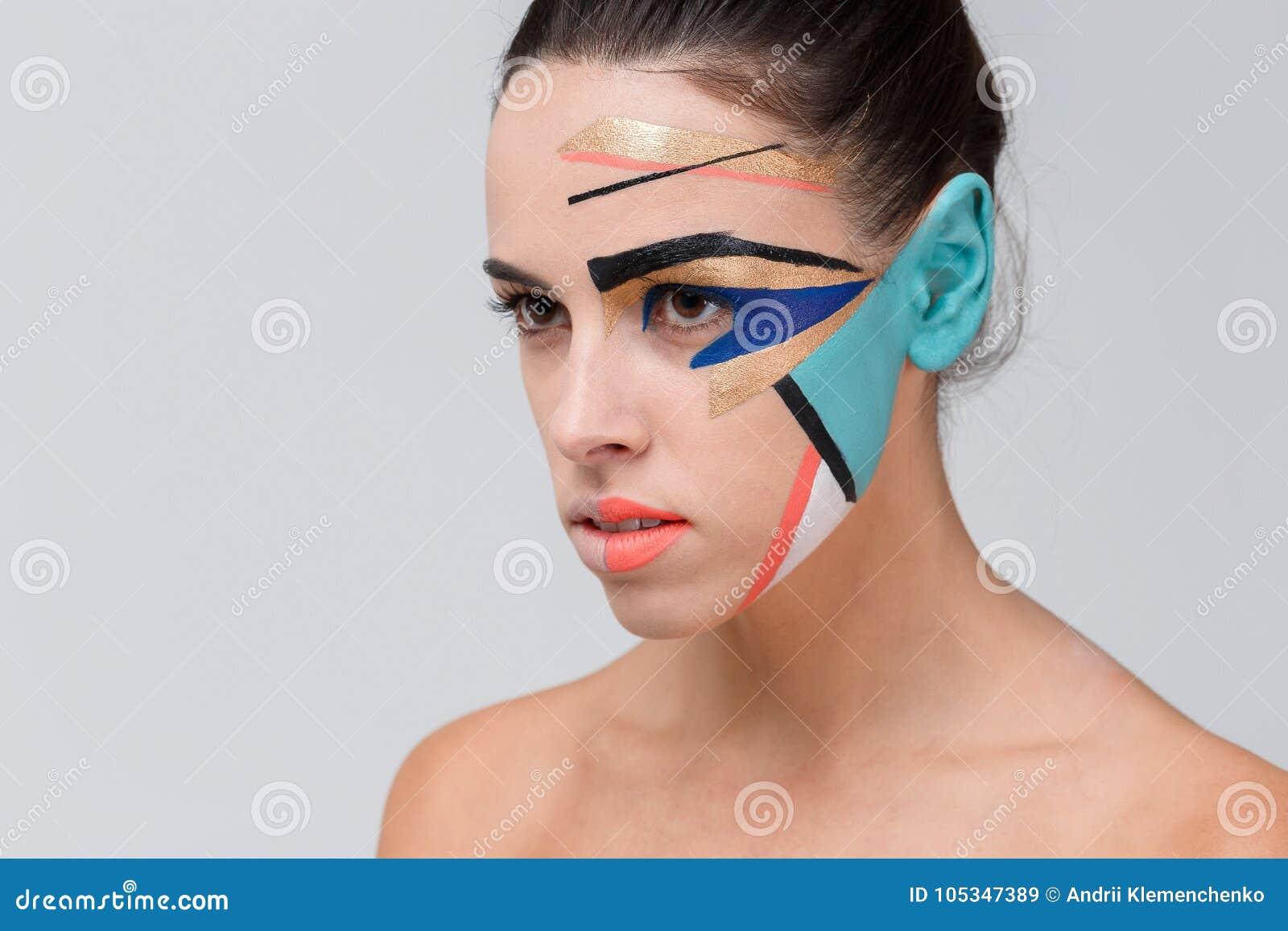 Una muchacha, con maquillaje geométrico creativo en su cara