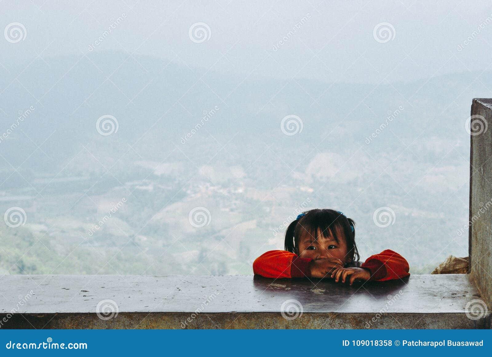 Una muchacha de la tribu de la colina que mira a su amigo mientras que están jugando o