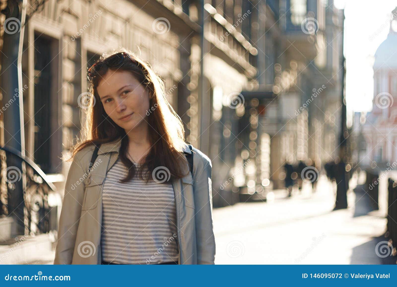 Una muchacha del estudiante se coloca en el fondo de una calle de la ciudad