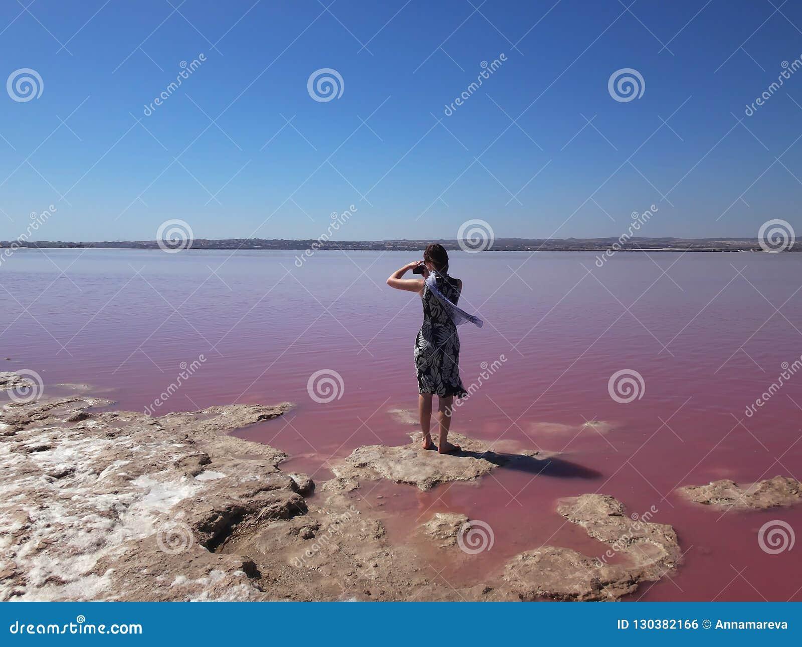Una muchacha en fotografías ligeras del vestido y de seda de la bufanda un lago rosado Torrevieja, España
