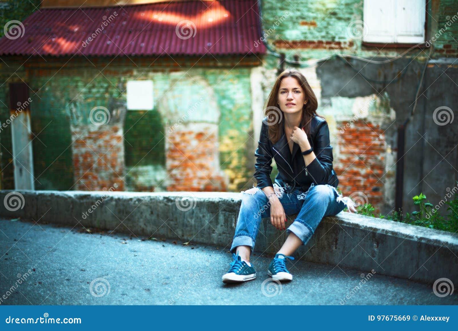 edf0cfcb9aa una-muchacha-en-una-chaqueta -de-cuero-vaqueros-y-zapatillas-de-deporte-el-sentarse-cerca-de-un-r-97675669.jpg