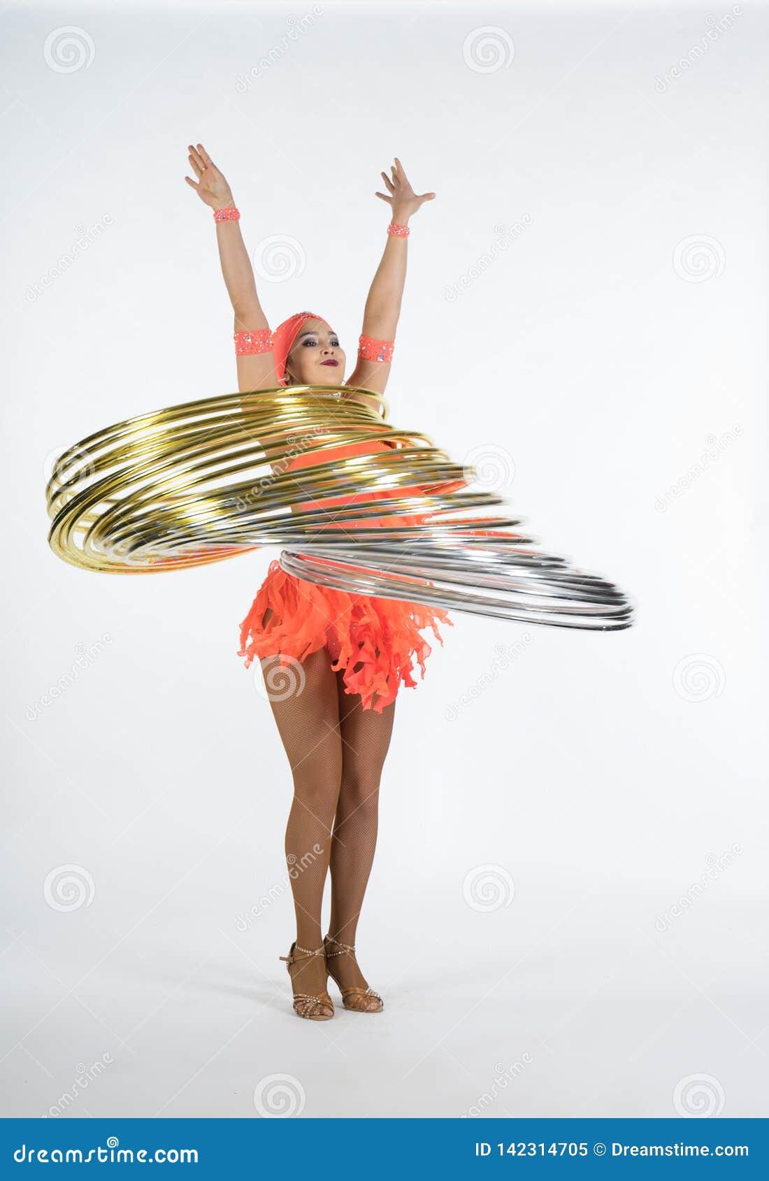 Una muchacha encantadora realiza elementos del circo con un aro del hula