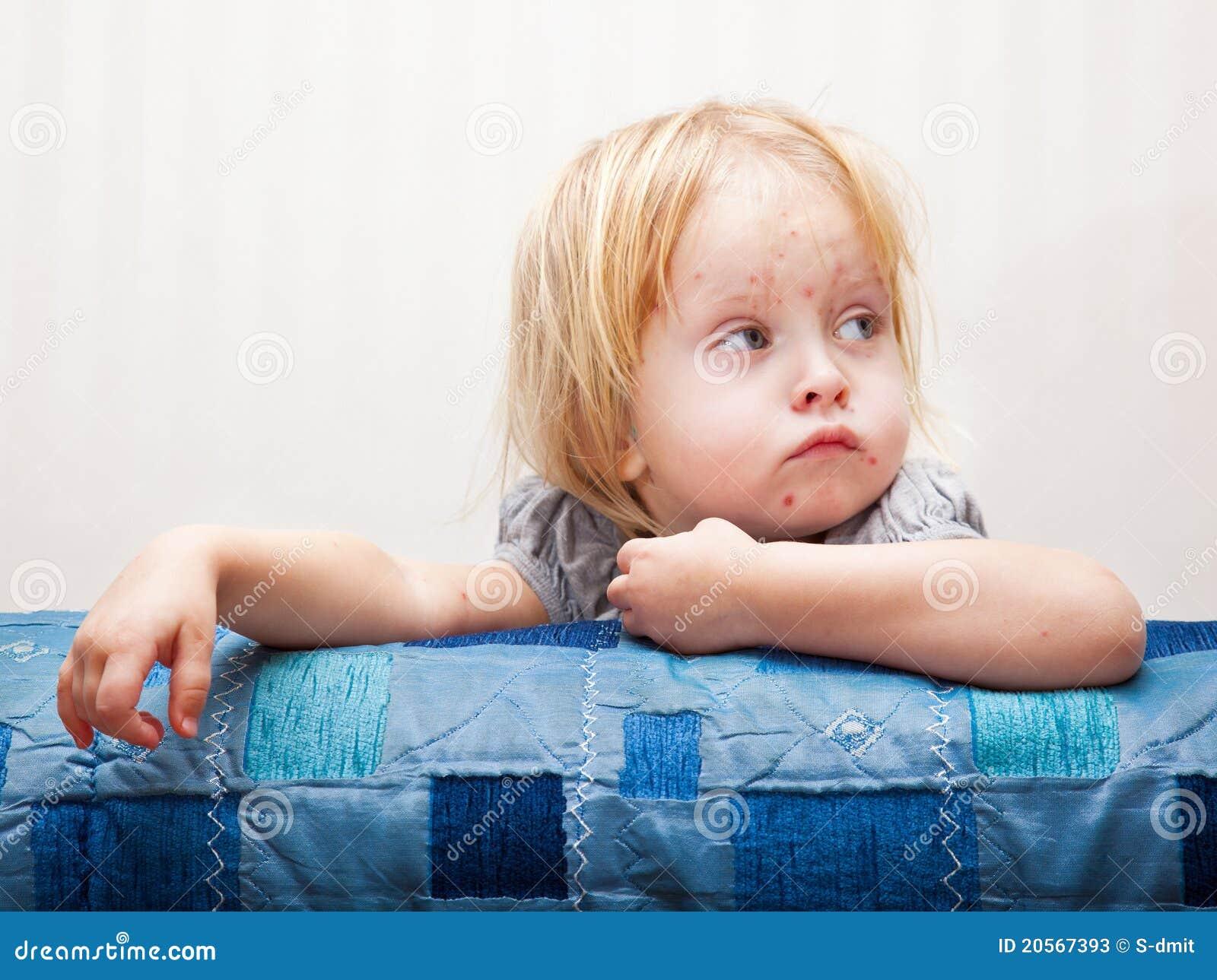 Una muchacha enferma se está sentando cerca de la cama
