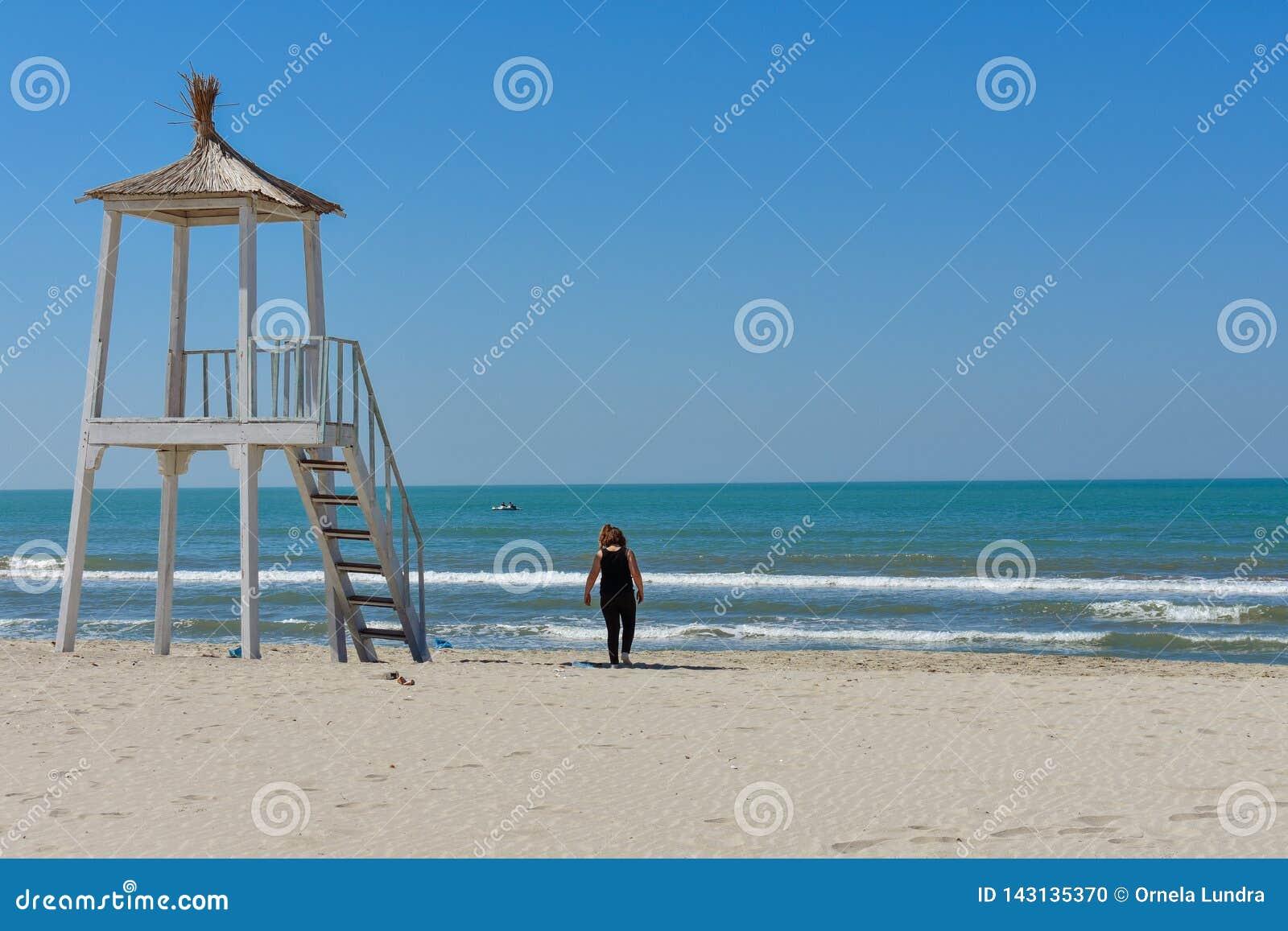 Una muchacha está caminando alrededor de la playa y está disfrutando del día soleado