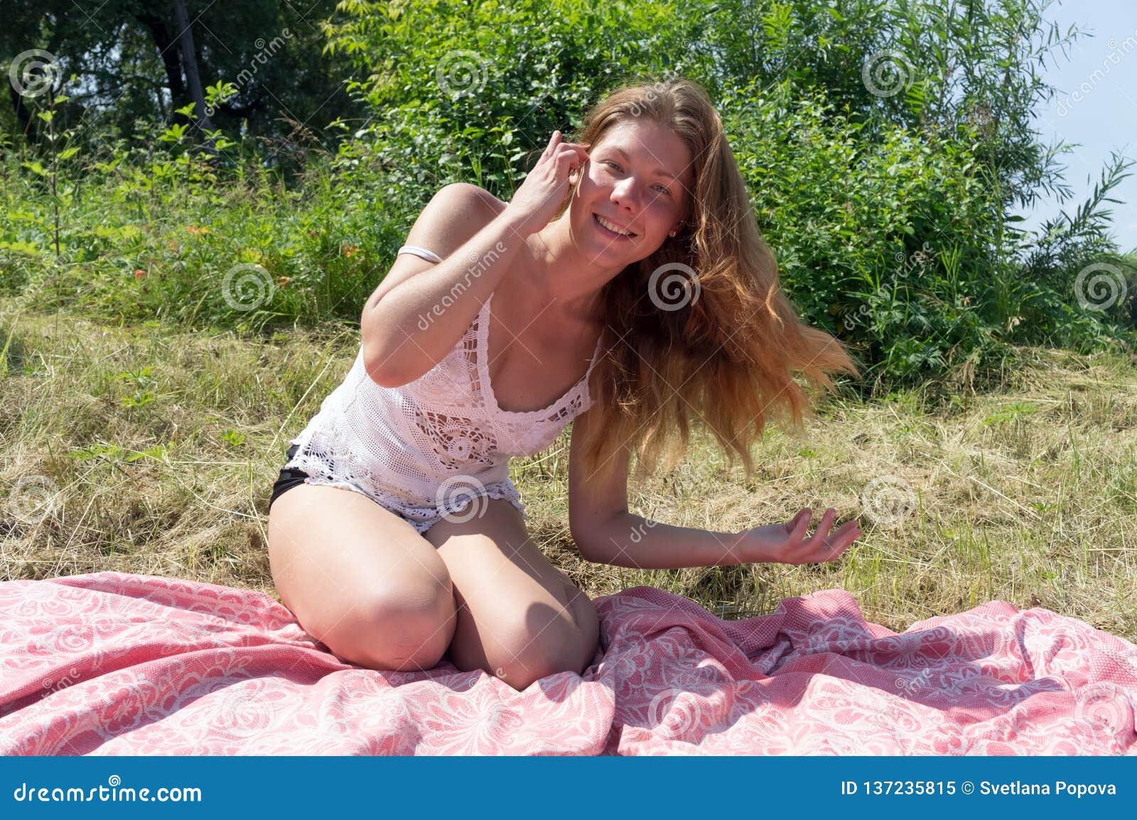 Una muchacha feliz se endereza el pelo rojo largo y toma el sol en una cubierta rosada en la hierba contra la perspectiva de un a