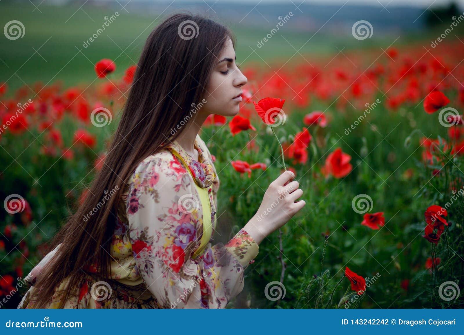 Una muchacha hermosa con el pelo largo y la piel natural, colocándose en un campo de amapolas rojas y sosteniendo una amapola roj