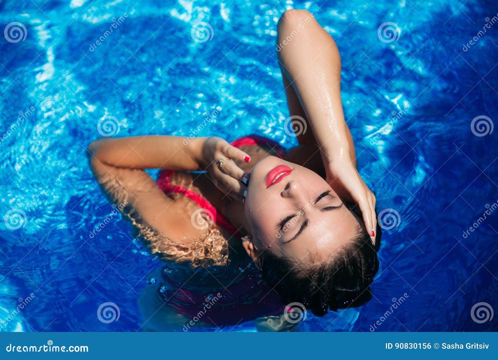 Una muchacha hermosa en un bañador rosado que toma el sol por la piscina tiempo soleado Verano