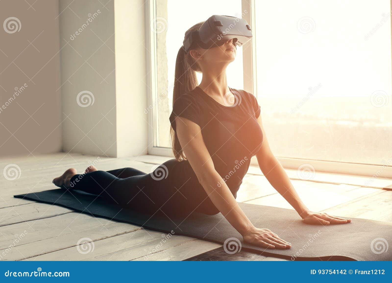 Una muchacha hermosa joven en vidrios de la realidad virtual hace yoga y aeróbicos remotamente Concepto futuro de la tecnología m