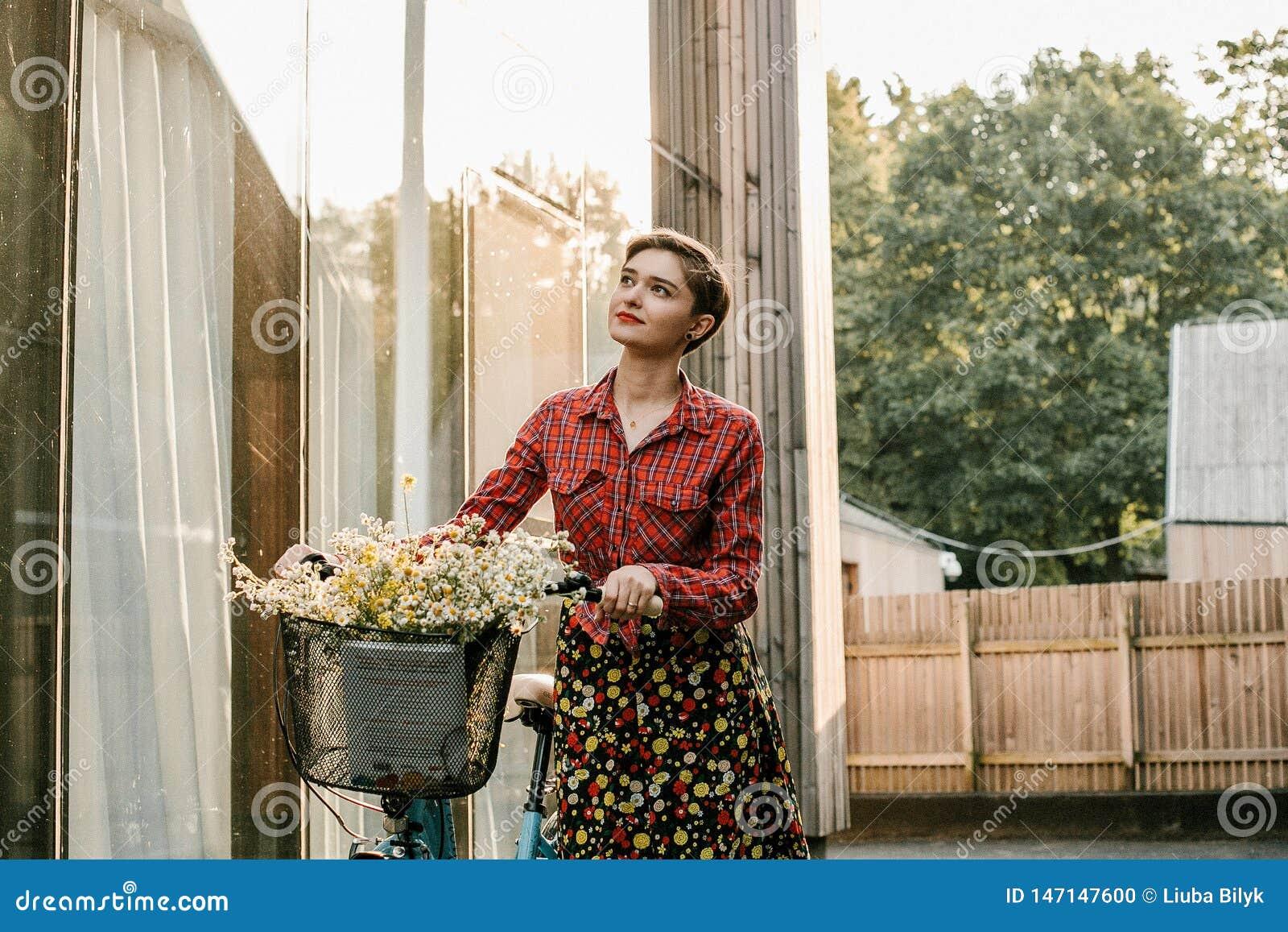 Una muchacha maravillosa viaja en bici El caminar en el aire libre Mujer hermosa con una cesta de flores Paseo de la bici