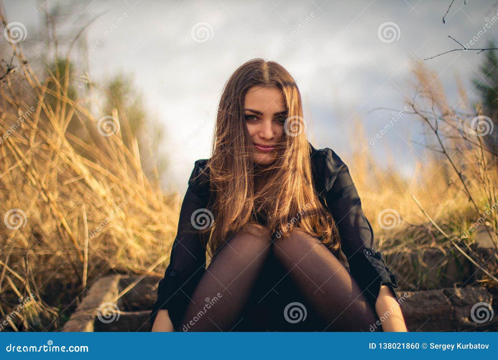 Una muchacha morena hermosa que se sienta en las escaleras Otoño Foto del arte
