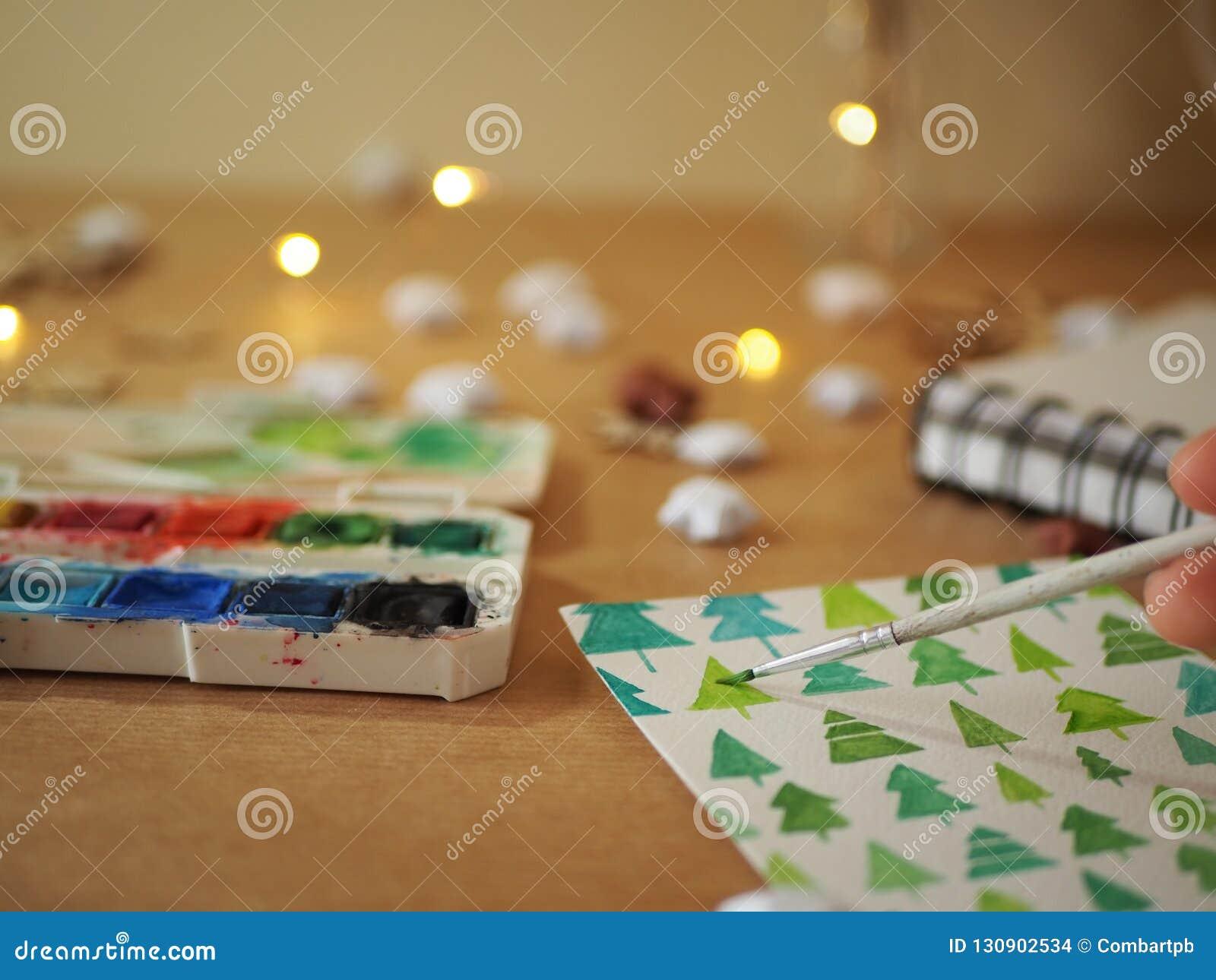 Una muchacha que pinta los árboles de navidad verdes en una hoja de papel blanca con las pinturas