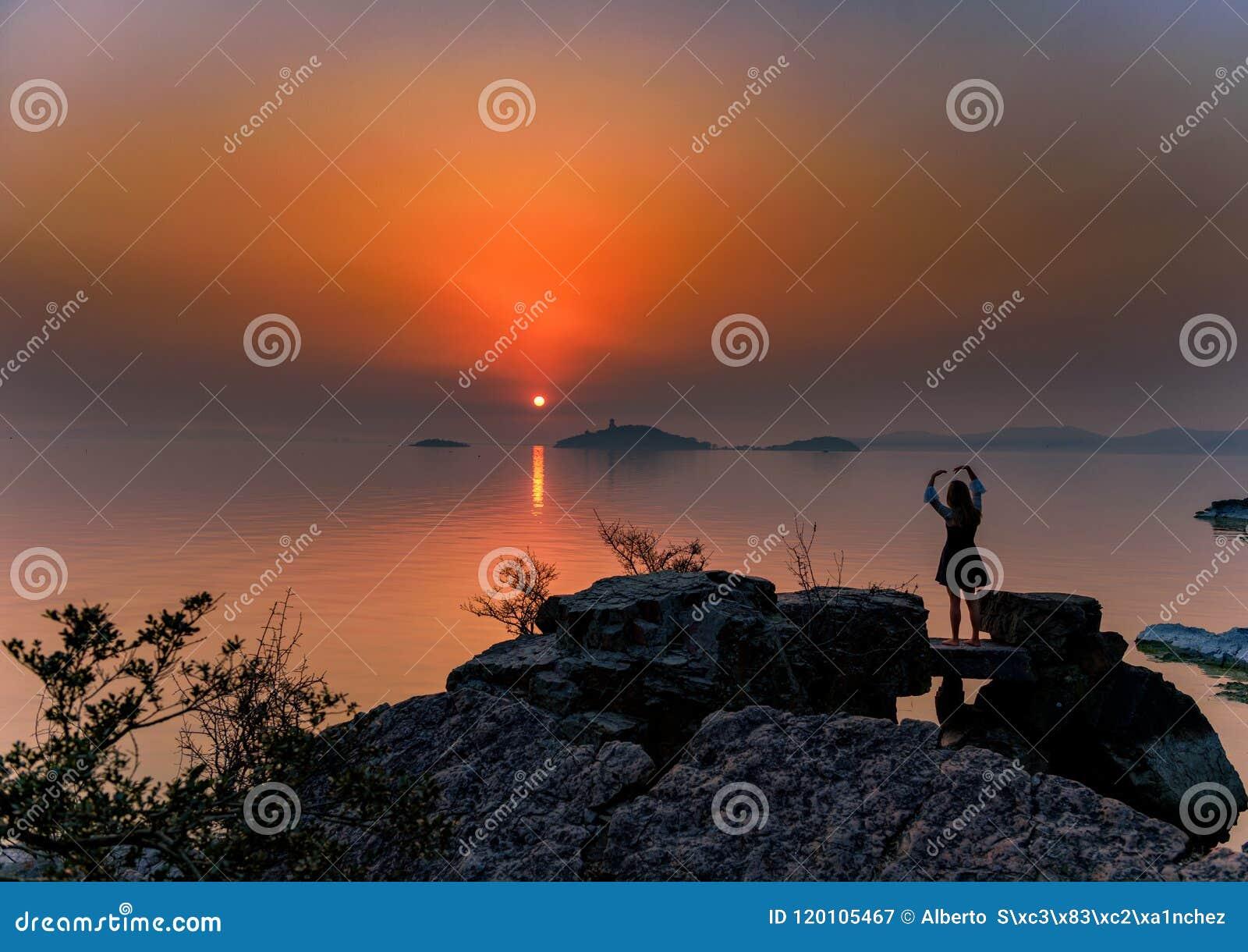 Una muchacha que presenta para la puesta del sol