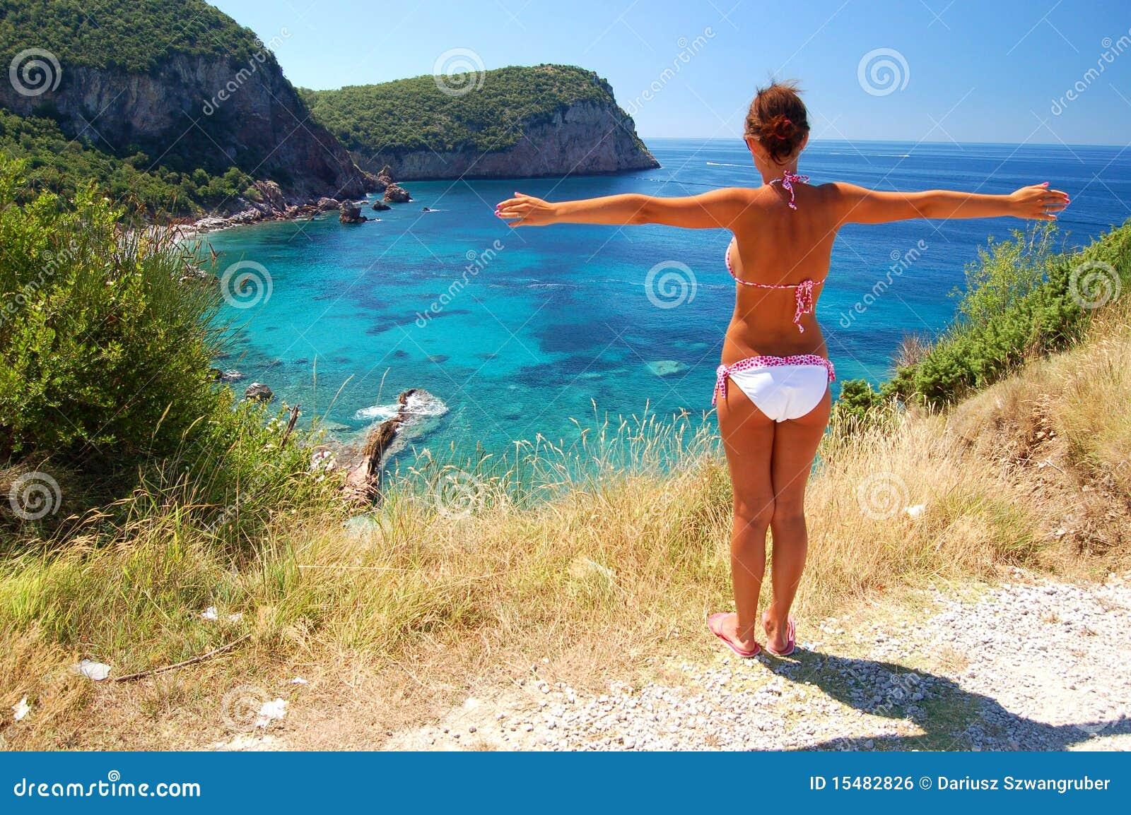 Una muchacha que se coloca sobre la playa rocosa